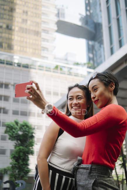 Joven asiático hembra amigos juntos tomando selfie en ciudad calle - foto de stock