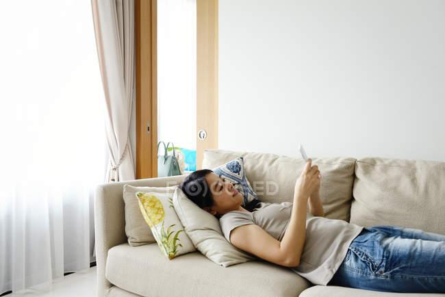 Випадковий азіатських брюнетки за допомогою смартфона в домашніх умовах — стокове фото