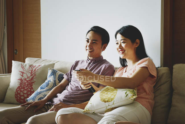 Adult asian couple together watching tv at home — Stock Photo
