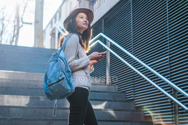 Jovem atraente asiático mulher usando smartphone em escadas — Fotografia de Stock