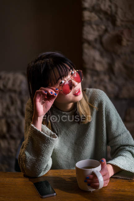 Young casual asian girl posing in cafe — Stock Photo