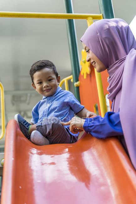 Jovem mãe muçulmana asiática e criança brincando no playground — Fotografia de Stock