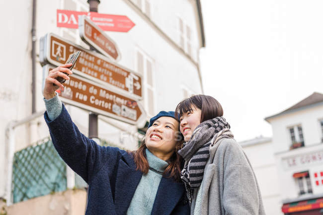 Young casual asian girls taking selfie on smartphone in city — Stock Photo
