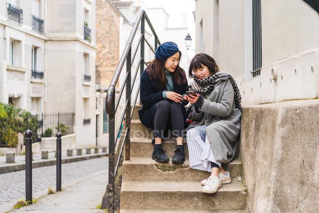 Giovani ragazze asiatiche casual utilizzando smartphone in città — Foto stock