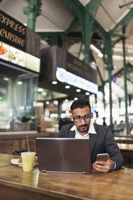 Bell'uomo d'affari indiano che usa il computer portatile e mangia nel caffè — Foto stock
