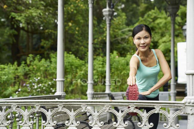 Літня жінка розігрів в ботанічного саду перед її run — стокове фото