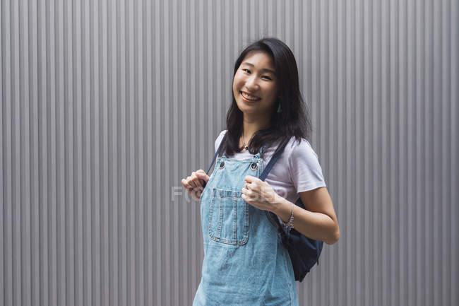 Молодая азиатская студентка колледжа позирует против серой стены — стоковое фото