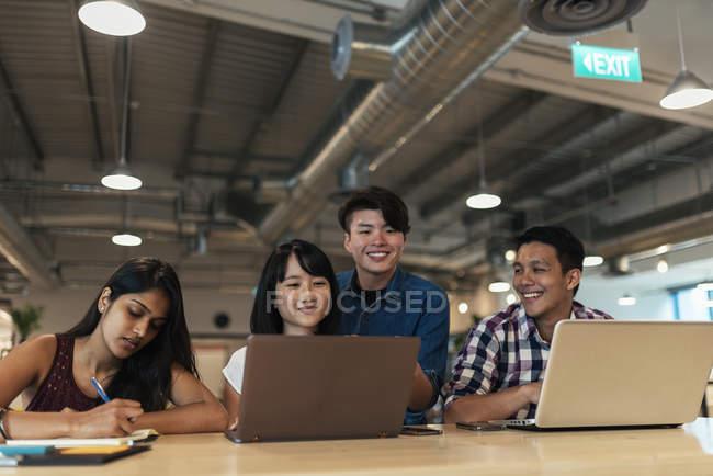 Jeunes gens d'affaires asiatiques travaillant ensemble dans un bureau moderne — Photo de stock
