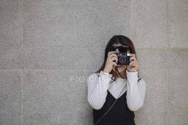 Pretty chinese long hair woman taking photo with camera — Stock Photo