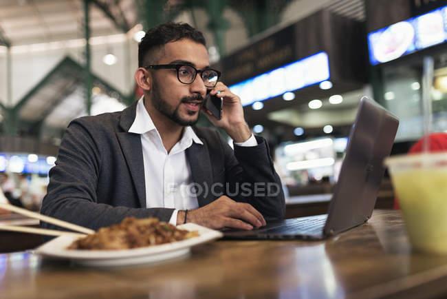 Schöner indischer Geschäftsmann mit Smartphone und Essen im Café — Stockfoto