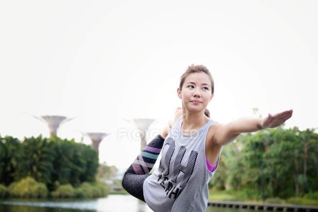 Giovane sportiva asiatico donna making stretching a parco — Foto stock