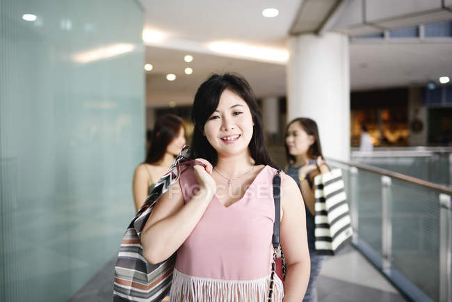 Joven asiático atractivo mujeres con compras bolsas - foto de stock