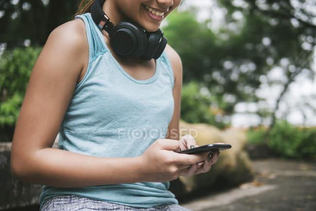 Jeune femme sportive asiatique à l'aide de smartphone dans le parc — Photo de stock