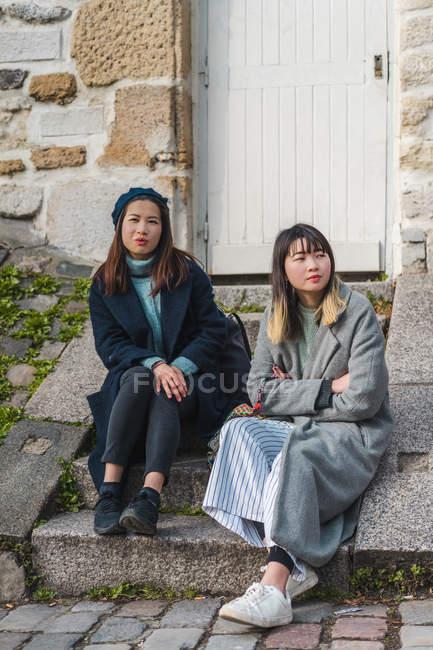 Lässige asiatische Mädchen sitzt auf der Treppe in der Nähe von Gebäude — Stockfoto