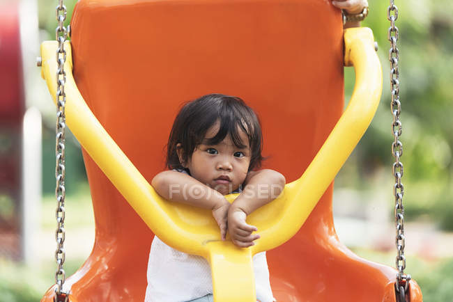 Cute adorable asian little girl on swing at playground — Stock Photo