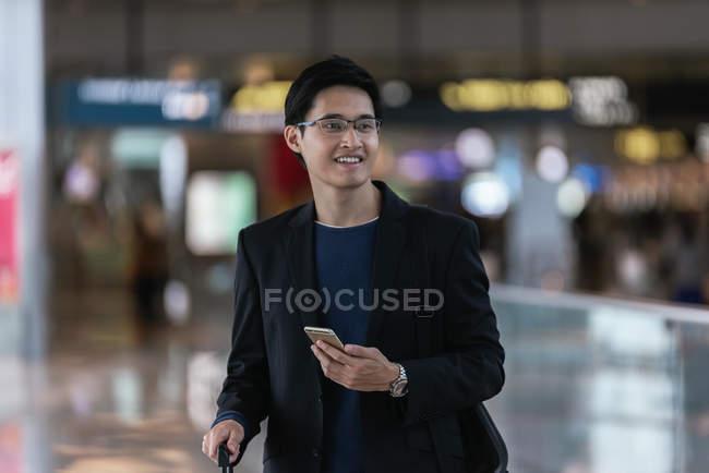 Uomo d'affari asiatico di successo utilizzando smartphone in aeroporto — Foto stock