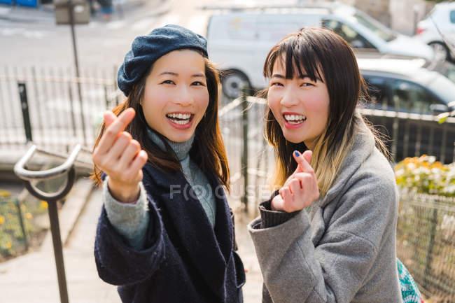 Giovani casual asiatico ragazze mostrando cuore gesto — Foto stock