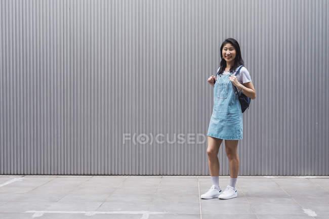 Giovane studente di college asiatico posa contro muro grigio — Foto stock