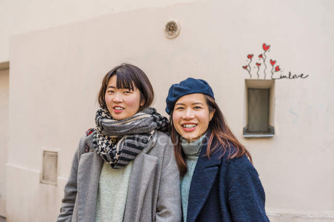 Young casual asian girls posing on city street — Stock Photo