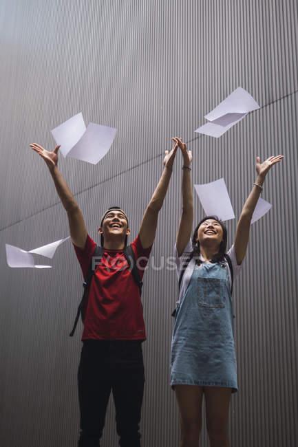 Junge asiatische College-Studenten werfen Papier in die Luft — Stockfoto