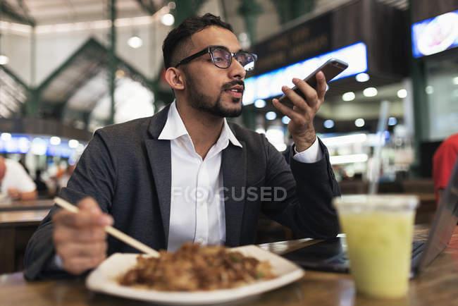 Красивый индийский бизнесмен, пользующийся смартфоном и питающийся в кафе — стоковое фото