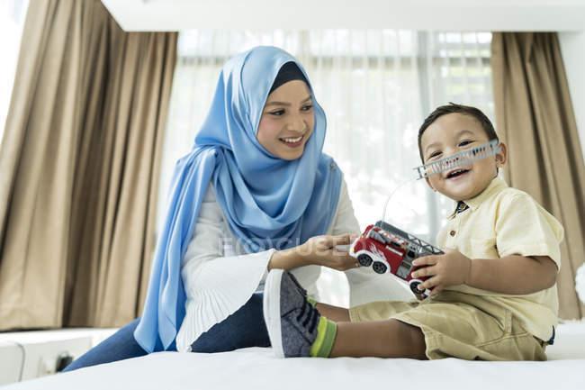 Jovem mãe muçulmana asiática e se divertindo em casa com brinquedos de criança — Fotografia de Stock