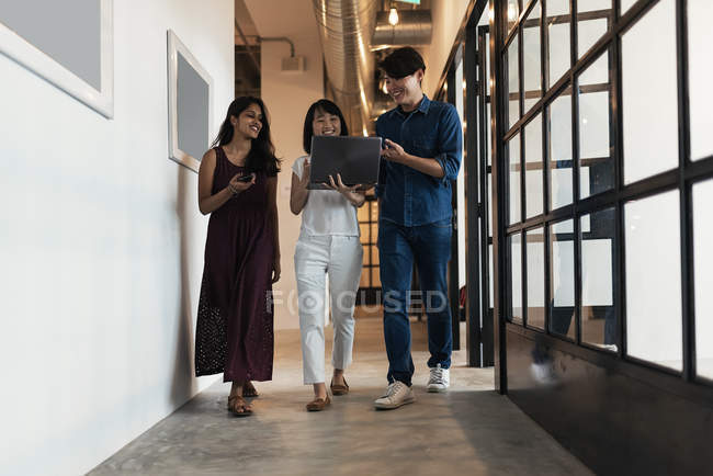 Young asian people at work with laptop in modern office — Stock Photo