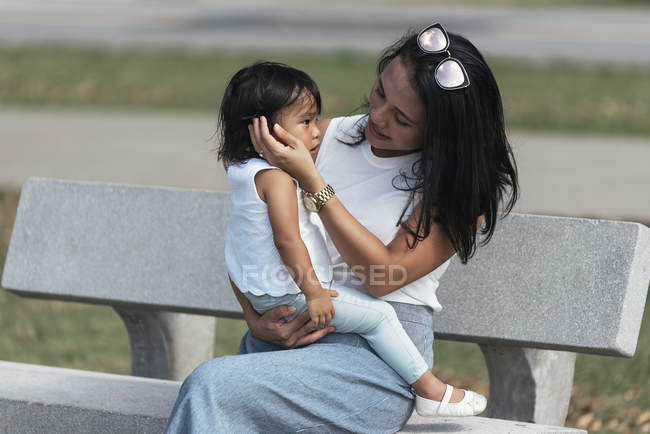 Cute adorable asian little girl on bench with mother — Stock Photo
