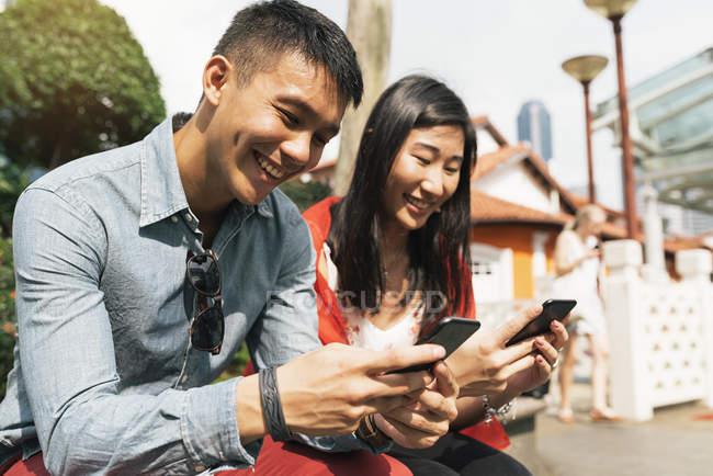 Щасливі азіатських молодят використання смартфонів в китайському кварталі — стокове фото