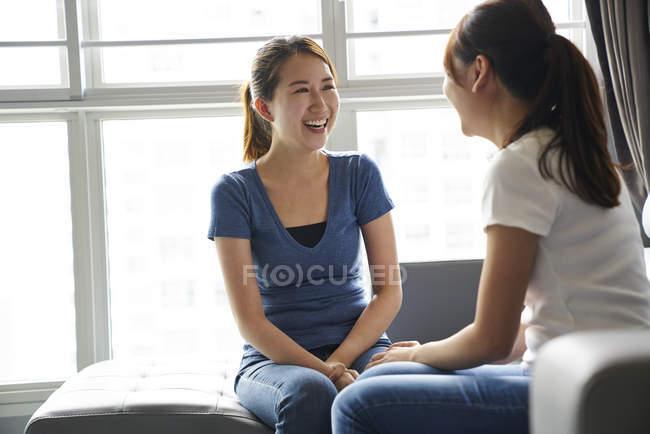 Giovani sorelle che si ritrovano in salotto — Foto stock