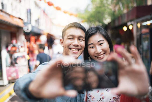 Jeune couple asiatique heureux prenant selfie dans Chinatown — Photo de stock