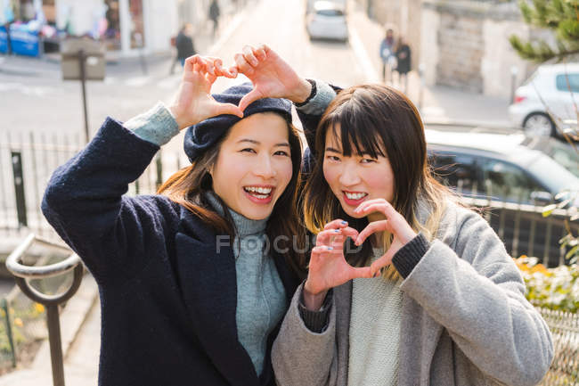 Lässige asiatische Mädchen schob Herzen mit den Fingern — Stockfoto