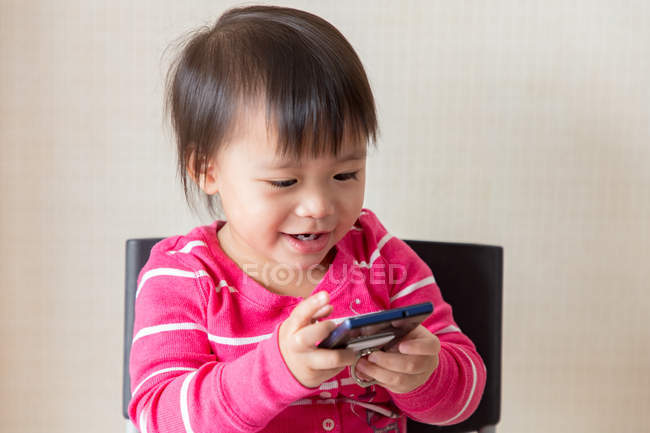 Young little asian toddler girl using smartphone — Stock Photo