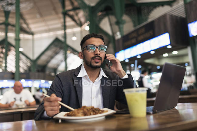 Hombre de negocios indio guapo usando teléfono inteligente y comer en la cafetería - foto de stock