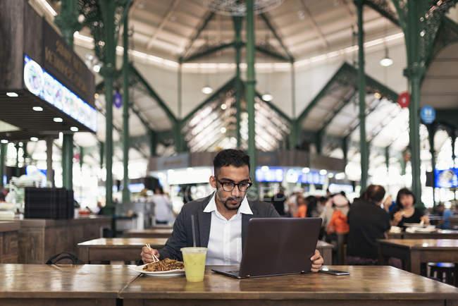 Bel homme d'affaires indien utilisant un ordinateur portable et manger dans un café — Photo de stock