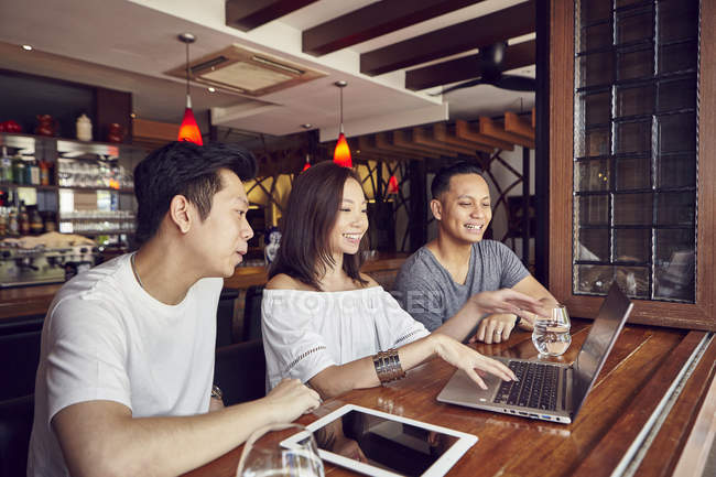 Happy young asian friends together working with laptop in bar — Stock Photo