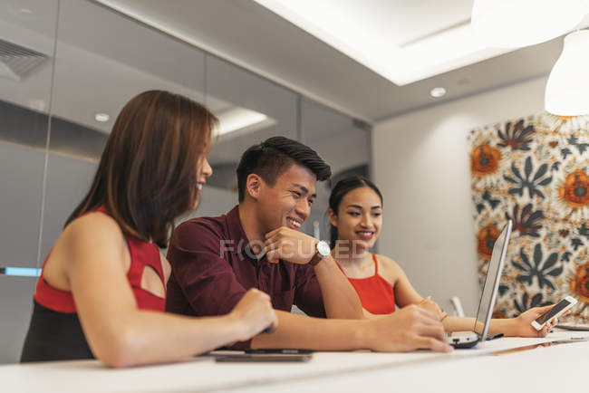 Asian business coworkers working with laptop and smartphone in the office — Stockfoto
