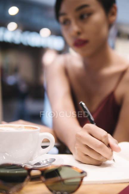 Привабливі азіатських брюнетки писати замітки в кафе — стокове фото