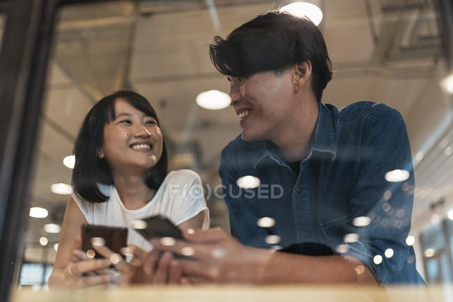Two young asian people at work with smartphones in modern office — Stock Photo