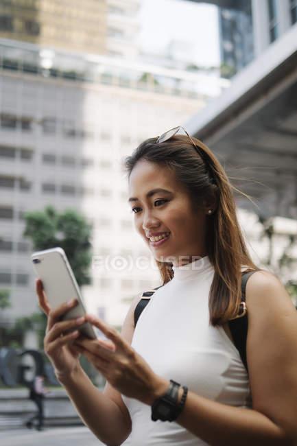 Joven asiático atractivo mujer usando smartphone en ciudad calle - foto de stock
