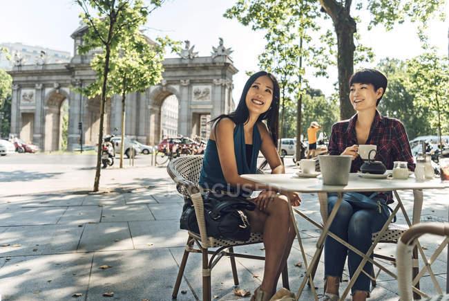 Japonés y chino turistas mujeres tomando café en la terraza cerca de la Puerta de Alcalá en Madrid, España. - foto de stock