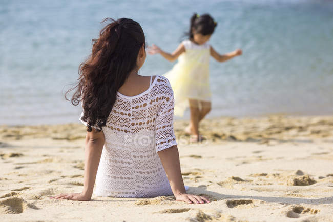 Happy young mother and daughter spending time together on beach — Stock Photo