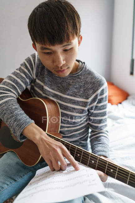 Young adult asian man playing on guitar at home — Stock Photo