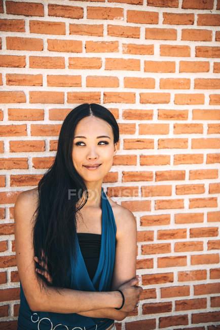 Long Hair asian woman posing on brick wall — Stock Photo