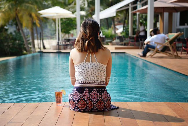 Rear view of young attractive asian woman relaxing by pool — Stock Photo