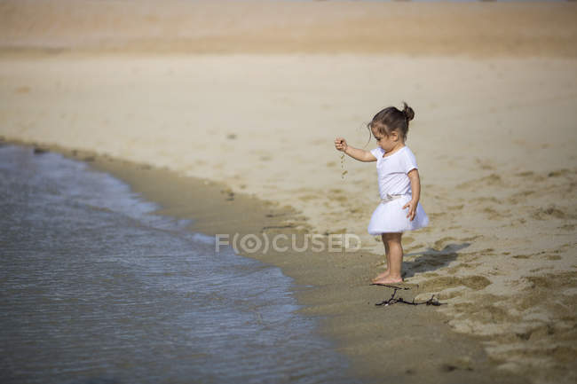 Little girl playing with sand on beach — Stock Photo