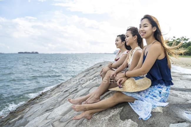 Três jovens senhoras relaxando na praia. — Fotografia de Stock
