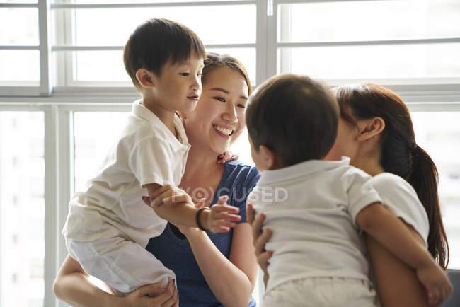 Giovani madri legame con i loro bambini nel soggiorno — Foto stock