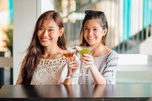 Attractive young asian women having drink — Stock Photo