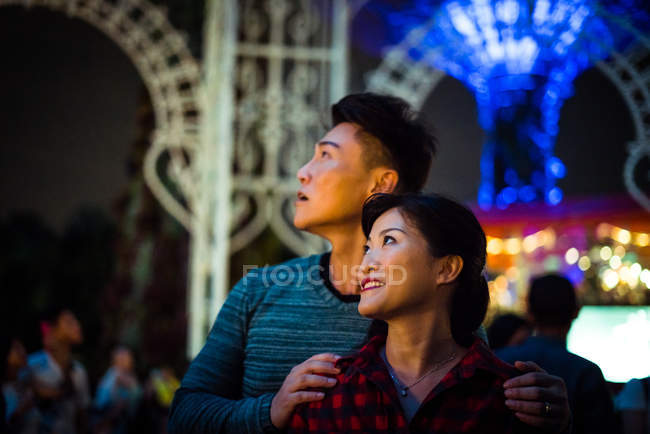 Happy asian couple  spending time together in amusement park at christmas — Stock Photo